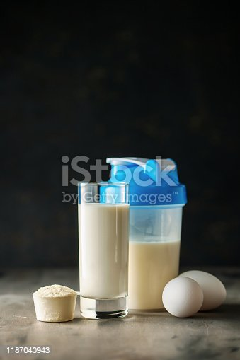 Protein shake in bottle, powder, bars, eggs and measuring tape on dark background.  Sport food concept.