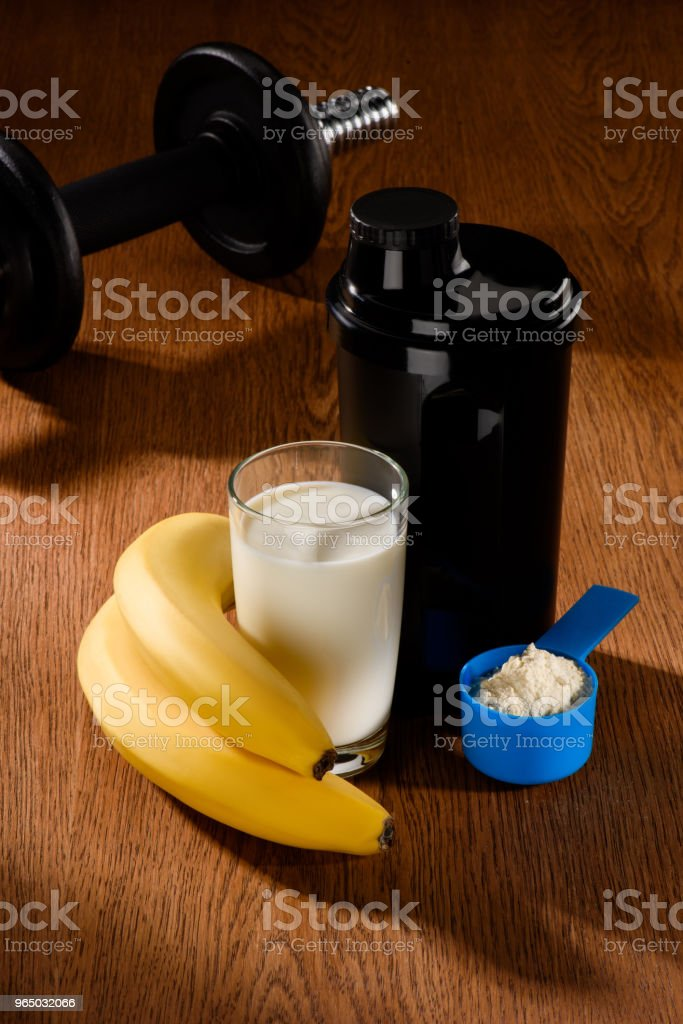 protein shake with dumbbell and bananas on wooden surface royalty-free stock photo