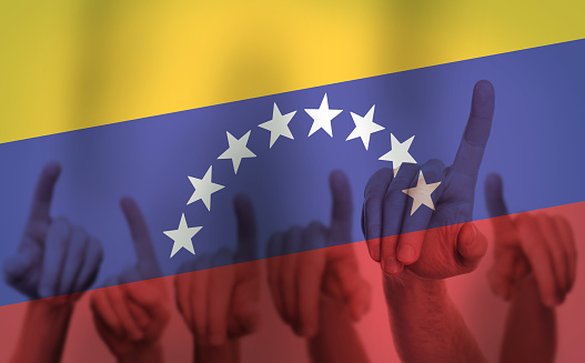 istock Protest Hands on the background of the Venezuela flag. Freedom concept 1141188736
