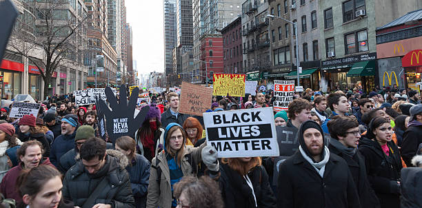 Protest in New York New York, NY USA - December 13, 2014: Angry protesters march against police brutality and grand jury decision on Eric Garner case on 6th Avenue riot stock pictures, royalty-free photos & images