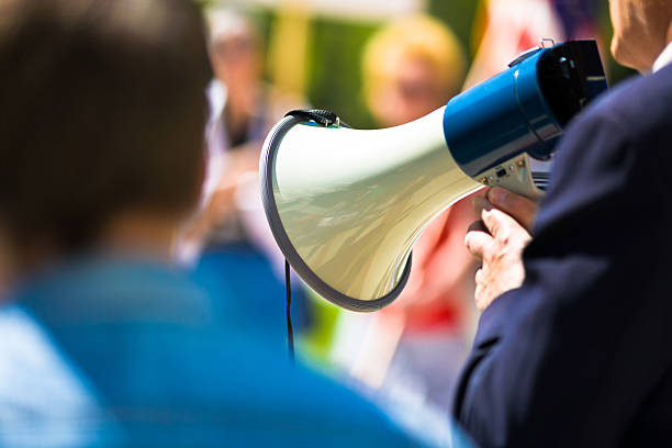 Protest Man holding a megaphone while speaking to a crowd. Very shallow DOF. labor union stock pictures, royalty-free photos & images
