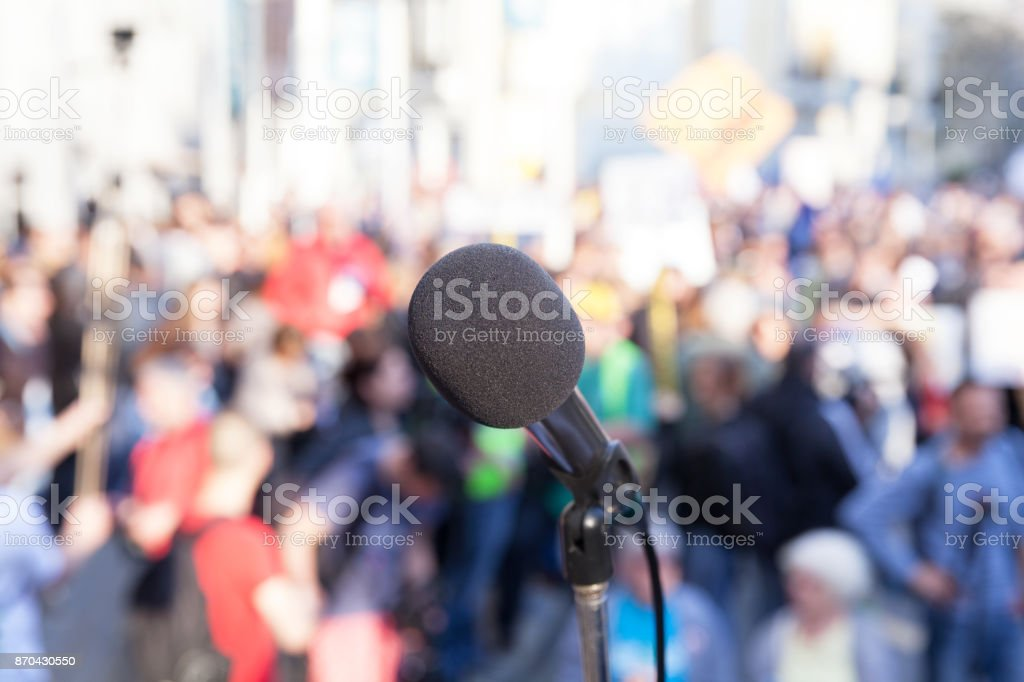 Protest. Public demonstration. Microphone in focus against blurred crowd. stock photo