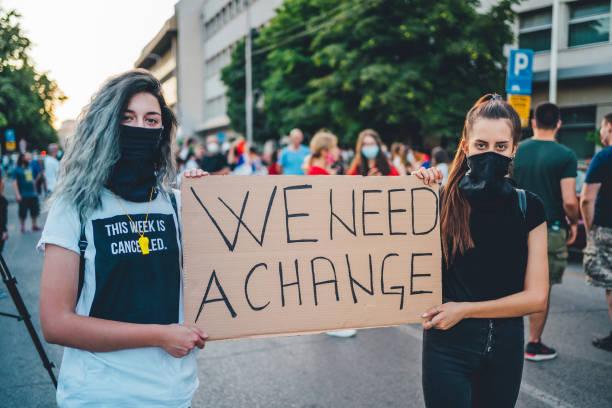 mujeres protestantes sosteniendo un cartel - civil rights fotografías e imágenes de stock