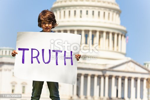 Child boy protest in front of the USA capitol in Washington holding sign saying  truth