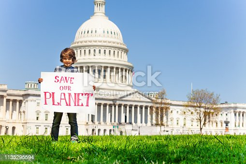 Child boy protest in front of the USA capitol in Washington holding sign saying save our planet