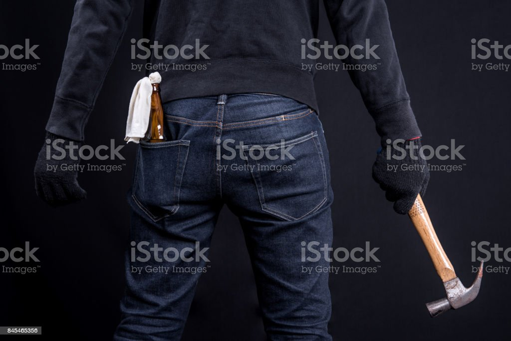 Protester or terrorist with Molotov cocktail as known as petrol bomb or bottle bomb and carrying hammer in black screen stock photo
