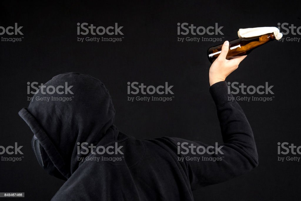 Protester or terrorist with Molotov cocktail as known as petrol bomb or bottle bomb in black screen stock photo