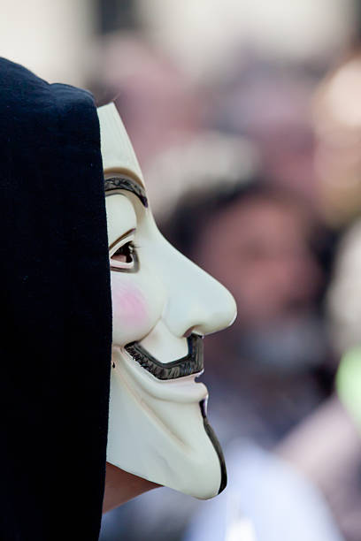 protester wearing a guy fawkes mask, anonymous - guy fawkes mask stock photos and pictures