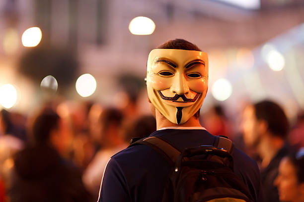 protester wearing a guy fawkes mask. - guy fawkes mask stock photos and pictures