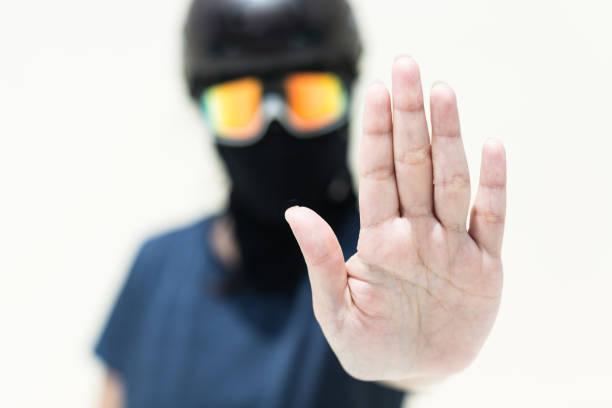 """protester con una máscara disfrazada, sosteniendo su mano arriba """"stop gesture"""" - civil rights fotografías e imágenes de stock"""