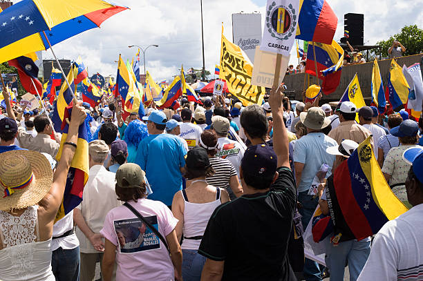 protesters against venezuelan government in a multitudinous parade - venezuela stock photos and pictures