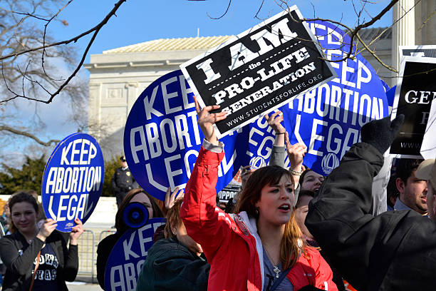 Protesters Chanting At The U.S. Supreme Court Washington D.C., USA - January 22, 2015; A Pro-Life woman clashes with a group of Pro-Choice demonstrators at the U.S. Supreme Court.  pro choice stock pictures, royalty-free photos & images