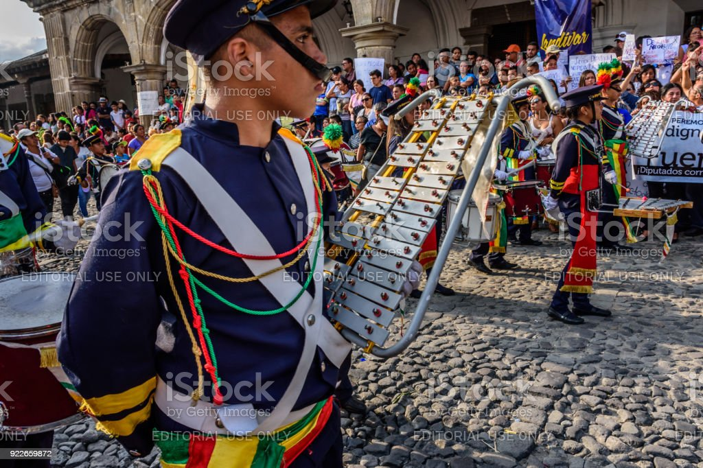 Protesters & marching band on Guatemala's Independence Day, Antigua, Guatemala stock photo