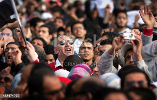 istock protesters watching a military helicopter fly low above liberation square 458474279