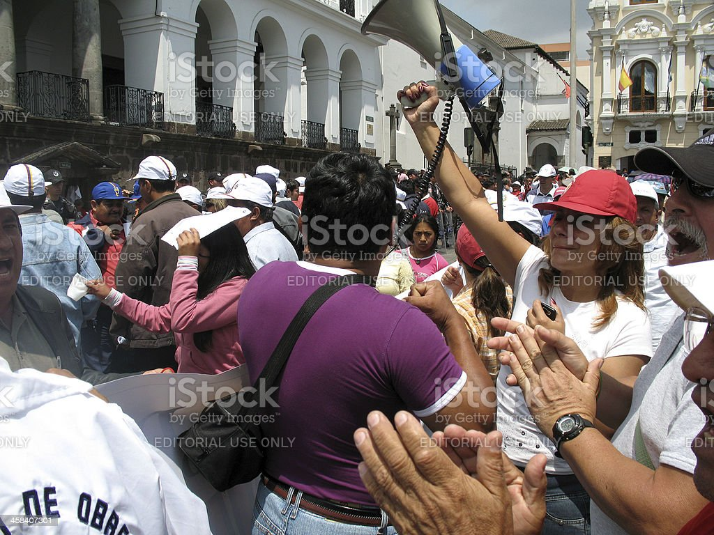 Protesters with megaphone outside Presidential Palace in Quito royalty-free stock photo