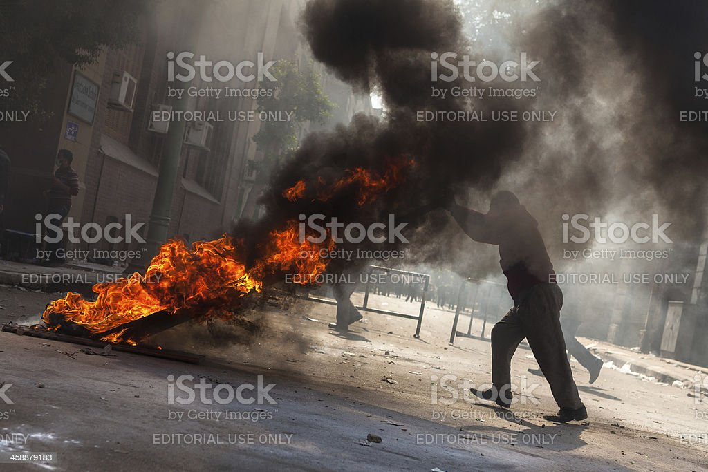 Protestor blocking street with fire royalty-free stock photo