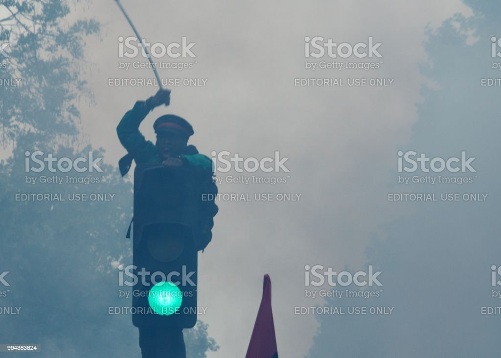 Protestor climbs a traffic light to express his anger against French President Macro's government, among other issues, on the streets of Paris stock photo