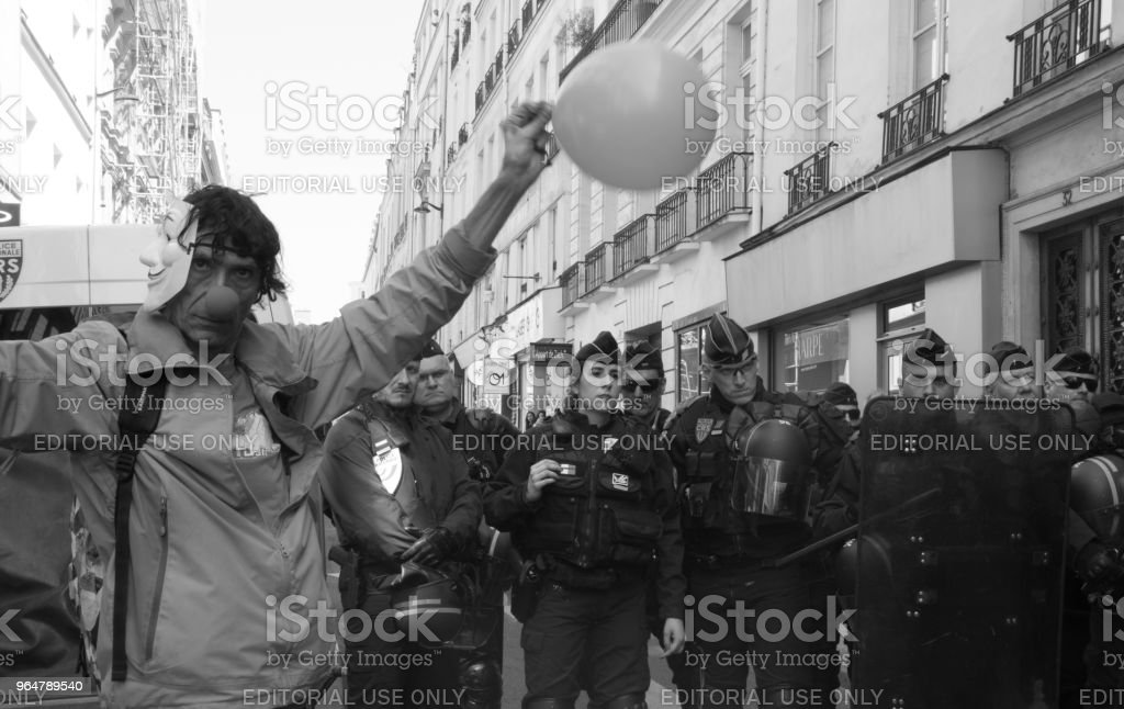 A protestor dressed up as a clown with a balloon stands next to French riot police stock photo