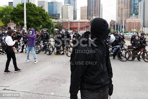 Seattle, USA - May 1, 2015: A protest wearing a gas mask on Denny way facing off with the Seattle police late in the day during the anti capitalist protest.