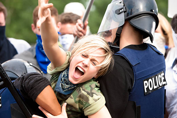 Protestor Trying to Get Through Police Barricade  riot police stock pictures, royalty-free photos & images