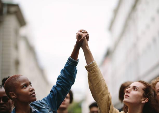 manifestantes haciendo manifestaciones en la calle - civil rights fotografías e imágenes de stock
