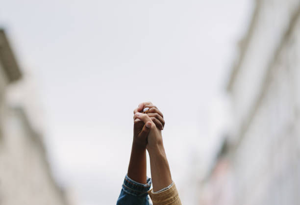 Protestors hands raised up in the air stock photo