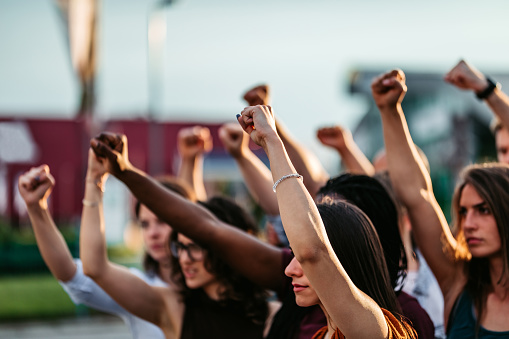 Protestors raising fists high above heads. Concept of protest, human rights, fighting.