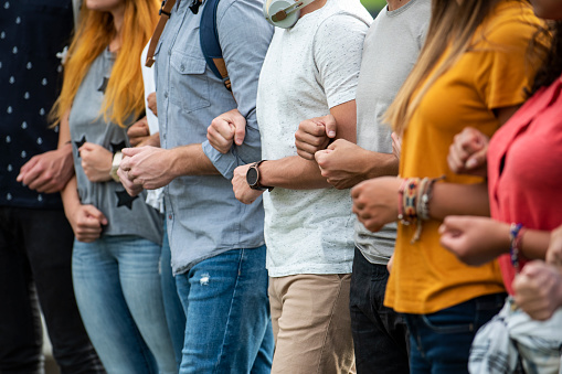Group of young male and female protestors with arms in arms and clenching fist while standing together outdoors