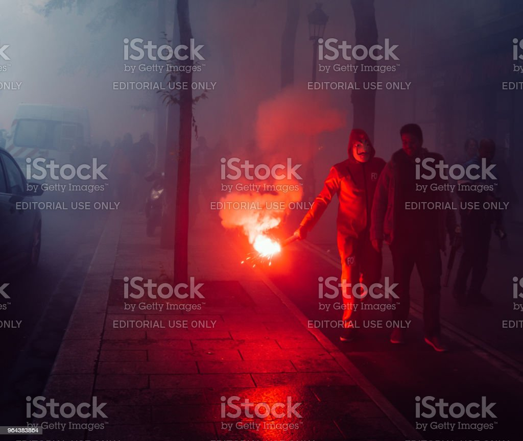 Protestors wearing a Guy Fawkes mask light gas canisters to express their anger against French President Macro's government, among other issues, on the streets of Paris stock photo