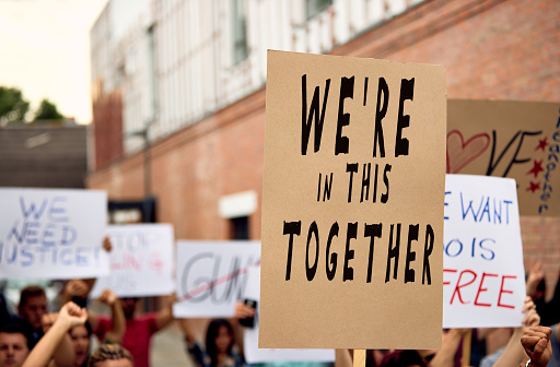 Unrecognizable person holding a placard with We are in this together inscription during public demonstrations.