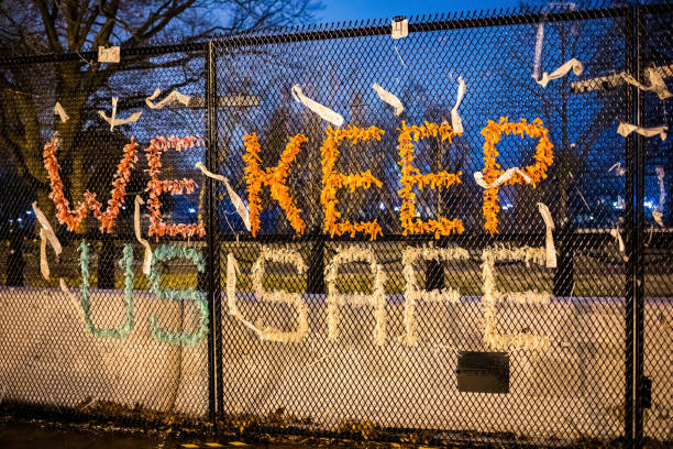 протесты знак мы держим нас в безопасности на заборе безопасности вокруг белого дома после беспорядков капитолийском холме - biden стоковые фото и изображения