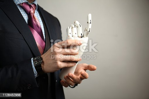 istock Prototype bionic prosthesis in hands of businessman. Restoration and treatment of the disabled 1128452956