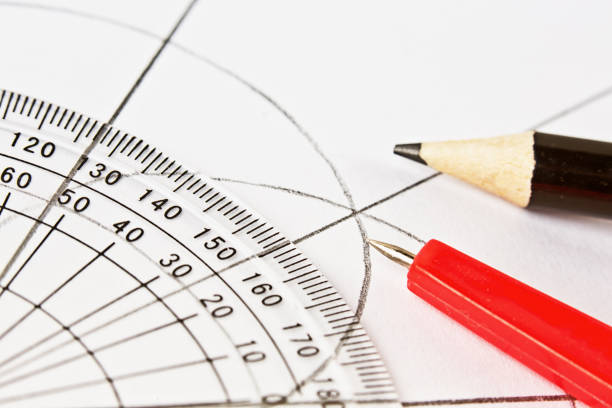 Protractor, compasses and pencil on diagram, all in close-up stock photo