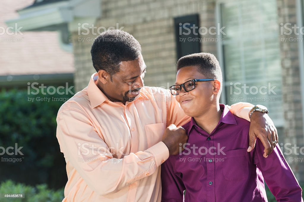 Proud African American father with teenage son stock photo
