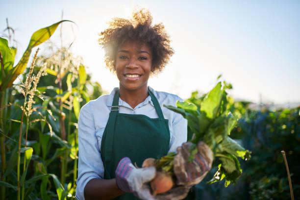 stolz auf afroamerikanische gärtner posieren für porträt - bauernberuf stock-fotos und bilder