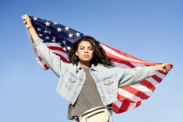アメリカ国旗を掲げて路上に立っている誇り高きアフリカ系アメリカ人女性。 - gen z ストックフォトと画像