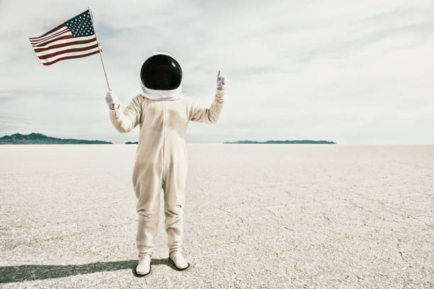 Proud American Astronaut with Flag Photo of a proud American astronaut, wearing a toy helmet and an adult size onesie, proudly holding an American flag in one hand while giving the number one sign with the other bonneville salt flats stock pictures, royalty-free photos & images