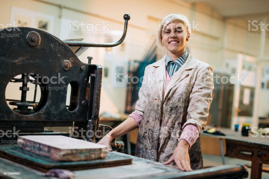 Proud artist posing in her workshop near printing press stock photo