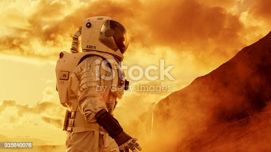 istock Proud Astronaut Confidently Walks on Mars Surface. Red Planet Covered in Gas and rock,  Overcoming Difficulties, Important Moment for the Human Race. 935640076
