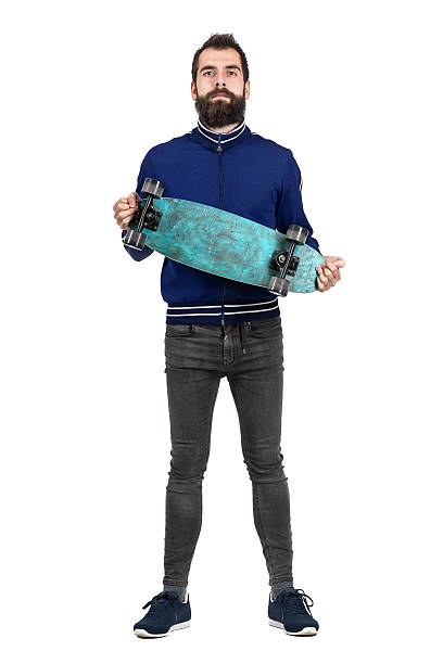 Proud bearded hipster carrying and showing skateboard to camera Proud bearded hipster carrying and showing skateboard to camera. Full body length portrait isolated over white studio background. men in tight jeans stock pictures, royalty-free photos & images