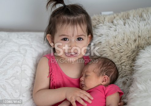 Adorable 2 year old holding her newborn sibling for the first time.
