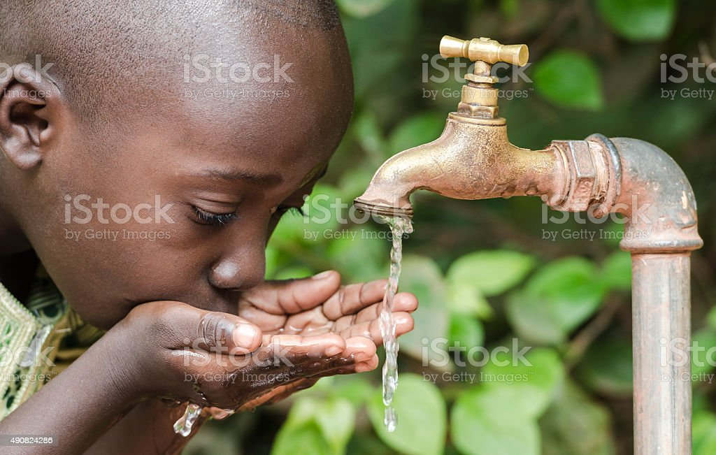 Proud Black Boy Drinking from a Water Tap Africa stock photo