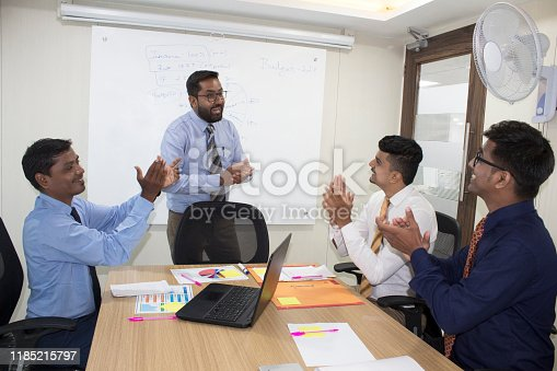 938516440 istock photo Proud business team clapping hands at meeting 1185215797