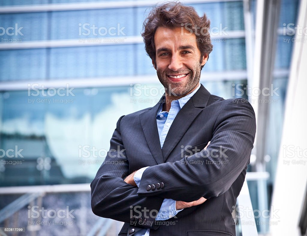 Proud Businessman smiling in front of his office stock photo