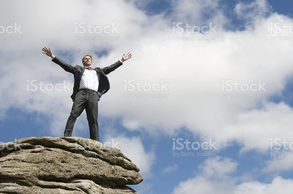 Proud Businessman Standing on Mountaintop Arms Spread stock photo