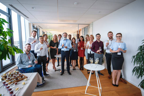 Proud CEO Posing with Staff of New Business Group portrait of bearded CEO in mid 50s standing with staff of new business and holding glass of sparkling wine for celebratory toast. publicity event stock pictures, royalty-free photos & images