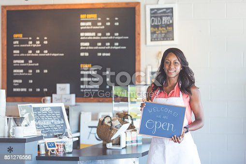 istock Proud coffee shop owner hold open sign on first day of business 851276556