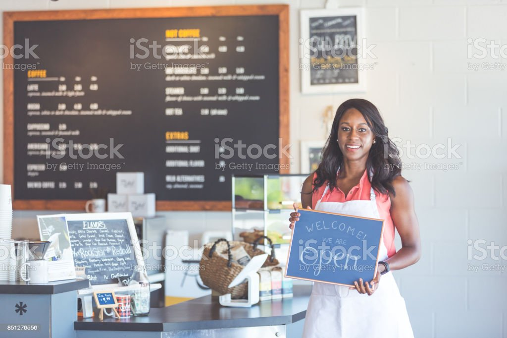 Proud coffee shop owner hold open sign on first day of business stock photo