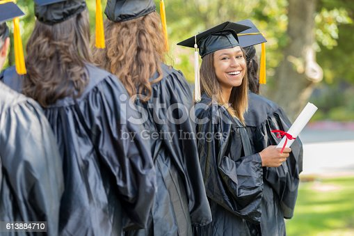 istock Proud college grad smiles after receiving diploma 613884710