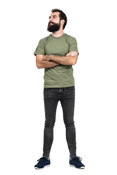 Proud confident bearded man with crossed arms looking up Proud confident bearded man with crossed arms looking up. Full body length portrait isolated over white studio background. men in tight jeans stock pictures, royalty-free photos & images